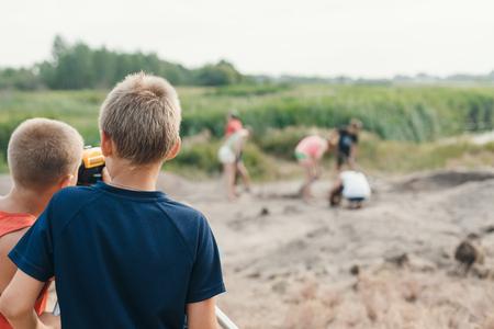 kleine jongen archeoloog maakt de meting afhankelijk van het optische niveau