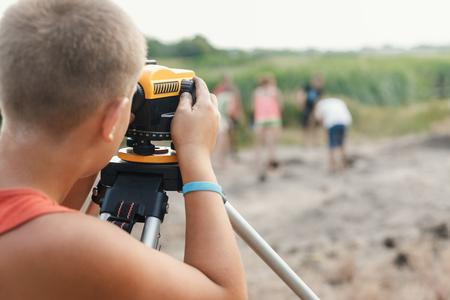 archeoloog kleine jongen maakt de meting afhankelijk van het optische niveau