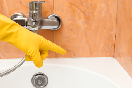 Hand in rubber glove indicates the mold under the sealant Stock Photo