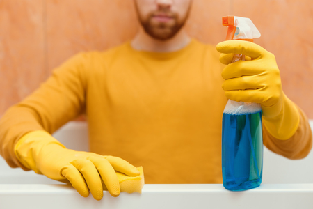 Man cleans bathroom with sponge and cleaning products
