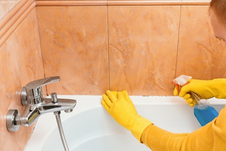 Man cleans bathroom with sponge and cleaning products from the mold Stock Photo