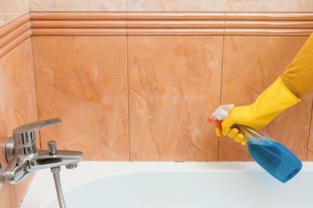Reiniger reinigt schimmel en meeldauw in de badkamer onder de kit