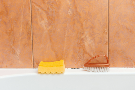 Sponge and brush are in the bathroom for cleaning mold Stock Photo