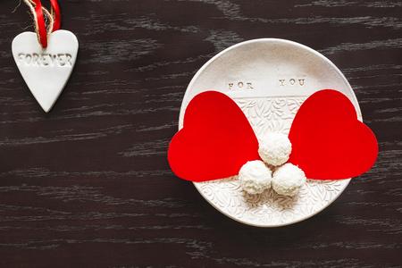 twee fluwelen harten op een kleiplaat van chocolaatjes op Valentijnsdag