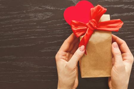 Een cadeau geven, verpakt in een handig pakket ter ere van Valentijnsdag. Bijgevoegde strik en rood hart, pluche Stockfoto