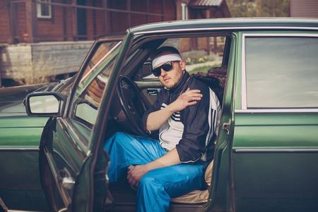 man in de jaren negentig zit achter het stuur van een auto Stockfoto