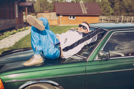 guy in the style of the 90s lies on the hood of an old car Stock Photo