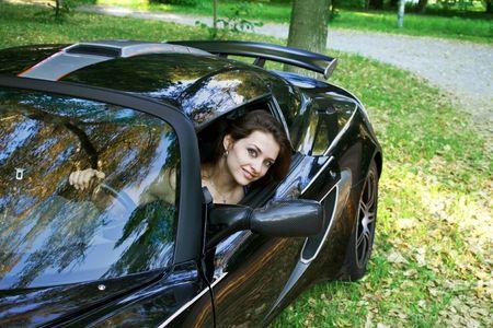PiÄ™kne Dziewczynka jest patrzÄ…c od samochodu sportu czarny