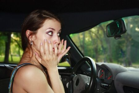 Shocked young woman in the car. photo