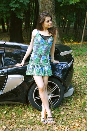 The sexual girl in standing near the sport car and looking at photo