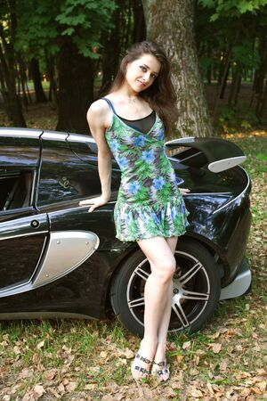 The sexual girl in standing near the sport car photo
