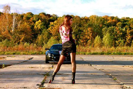 Sexy belle fille pr�s de voiture de sport sur route. Automne.  Banque d'images - 7891223