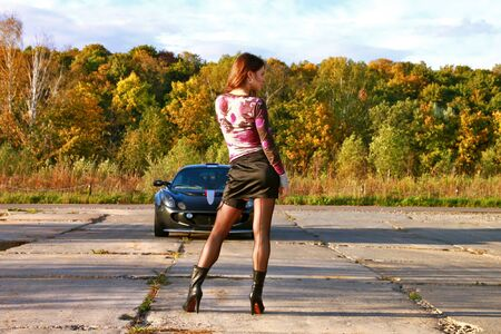 Racing day. Sexual driver standing near her sport car. Beautiful autumn. Good weather.  Stock Photo - 7891220