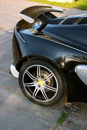 The black sport car with big wheels on road. photo