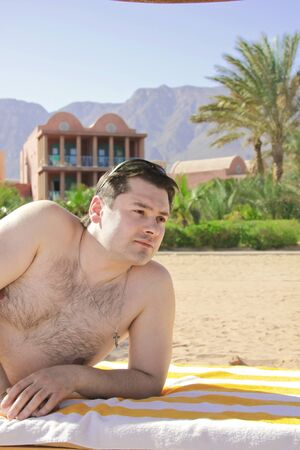 Man sunbathing on the beach on lounger and thinkfully looking at Stock Photo - 8691769