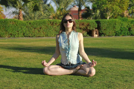 Beautiful young woman in the Lotus position, practicing yoga outdoor photo