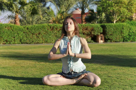 Beautiful young woman in the Lotus position with closed eyes, practicing yoga outdoor photo