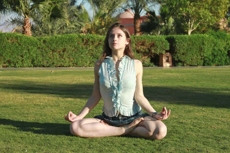 Beautiful female in the Lotus position looking up, practicing yoga outside photo