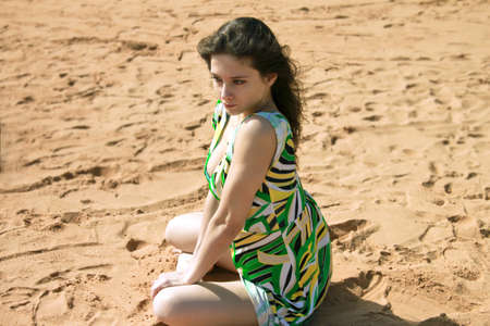 Sexy girl is sitting on the sand in green dress with passion eyes photo