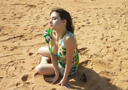 Sexy girl is sitting on the sand in green dress and looking at photo