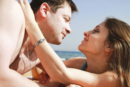 looks: Happy young couple having a rest on the beach and looking each other Stock Photo