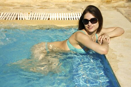 Sexual girl in bikini is relaxing in blue jacuzzi in glasses photo