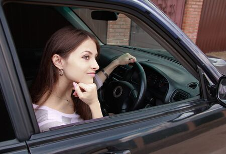 Thinking beautiful girl is sitting in the sport car and looking photo