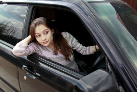 Surprising beautiful woman looking from the car to the road with big eyes photo