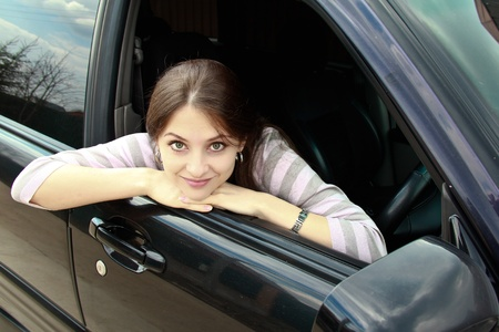 Portrait of beautiful girl looking out from window of car. Good weather. Funny mood photo