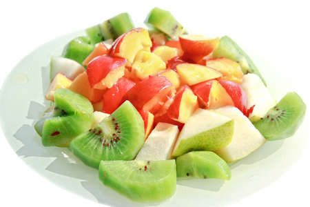 Plate of assortment of bright cut colorful fruits of kiwi, nectarine and pear photo