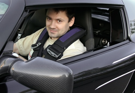 Young man, racer sitting in sport black car and looking from opened window with smiling photo