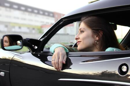 Beautiful girl relaxing in sport black car and looking from opened window on mirror outdoor. photo