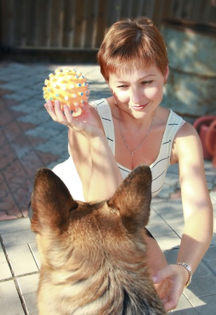 Beautiful woman holding the toy and playing with shepherd dog on yard. photo