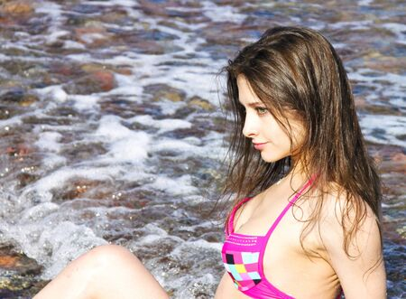 Portrait of beautiful girl sitting in the sea with wet long hair thoughtfully looking at photo