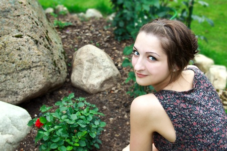 Beautiful girl sitting near the bush of red roses and big stone in garden photo