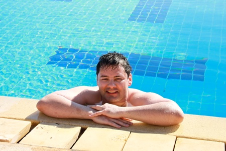 Smiling man having a rest in blue swimming pool photo