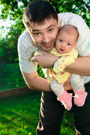 Father holding newborn joyful baby girl on the hands on nature green background Stock Photo - 10301840