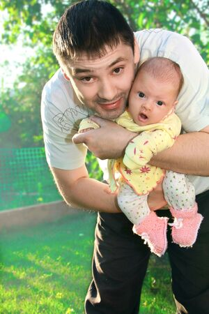 Father holding newborn joyful baby girl on the hands on nature green background photo