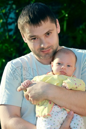 Handsome smiling man holding newborn serious baby girl on the hands photo