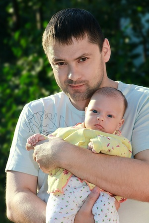Thoughtful man holding serious little baby on the hands in park on green background. Happy family looking in camera and thinking.  photo