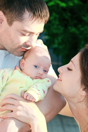 Beautiful mother and father looking at their little blue eyes baby on green nature background Stock Photo - 10365860