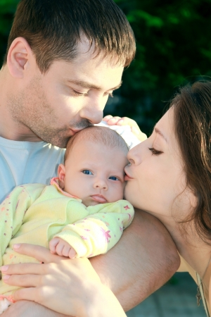 mom and dad: Parents kissing beautiful blue eyes baby girl on nature. Babe looking serious and thinking about. Happy family