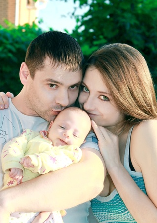 Happy family. Young mother and father kissing their little daughter with love on nature in the park. photo