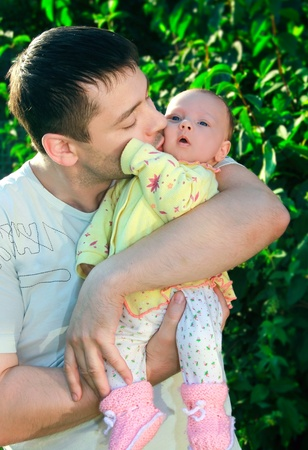 Handsome young father kissing his little baby on green tree background photo
