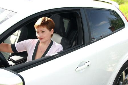 ventana abierta interior: Joven y bella mujer conduc�a el coche deportivo en el soleado d�a de verano