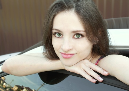 Macro portrait of beautiful bright girl with green eyes standing near the car and thinking photo