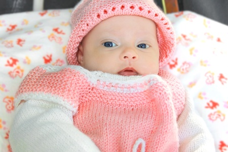 Macro portrait of little baby in pink hat and dress with blue eyes photo