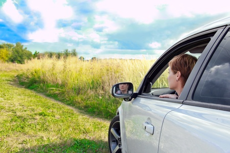 look inside: Beautiful woman looking from window of sport car in the field under bright blue sky Stock Photo