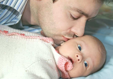Macro portrait of handsome father kissing little baby girl with love indoor photo