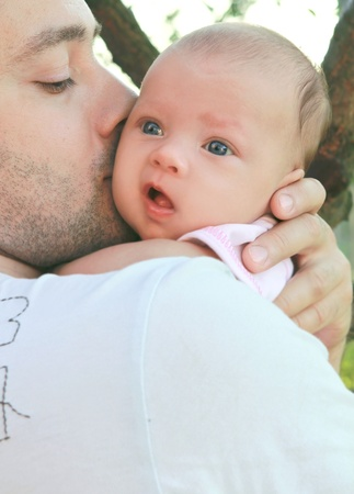parents: Father kissing little baby girl on the hands on nature background
